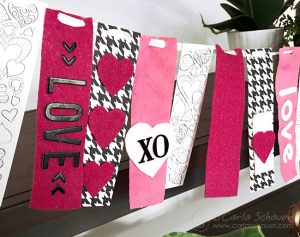 Make a Valentine Garland Decoration using free printable coloring bookmarks, and strips of fabric and paper. Adorable!