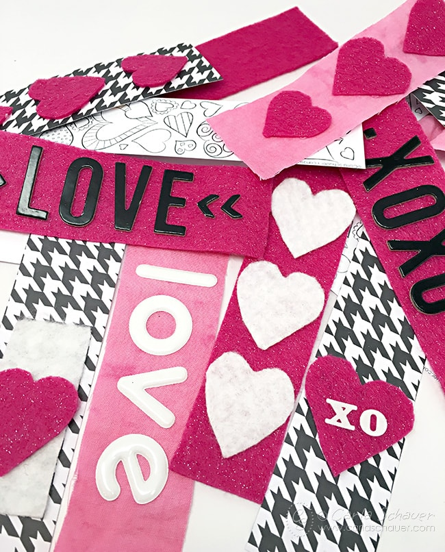 Use strips of fabric, printable coloring bookmarks, and patterned paper to make a Valentine Garland. Love this idea! Download the bookmarks at carlaschauer.com
